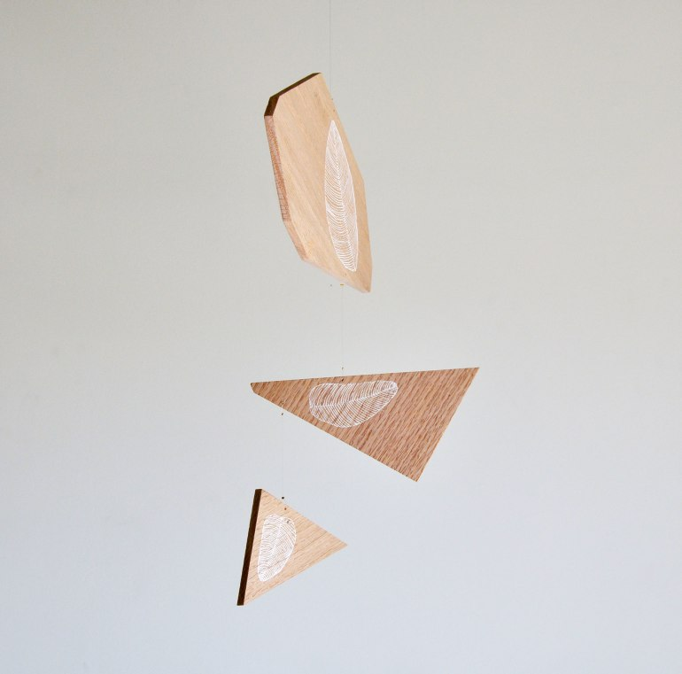 Out of Tune, a geometric wooden mobile with white line art leaves hand drawn
